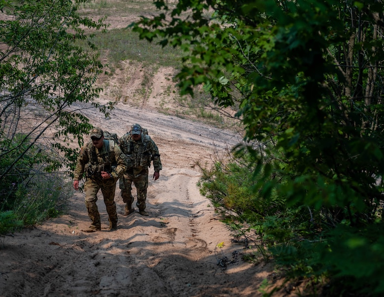 U.S. Army Staff Sgt. Wyatt Brown, left, 2-211th Army Regiment flight medic, and Sgt. Brandin Frey, 2-211th Army Regiment aircraft mechanic, walks up a hill in a simulated Combat Search and Rescue mission during Northern Strike (NS) 21-2 near Ontonagon, Michigan, Aug. 3, 2021. NS maximizes combat readiness by providing adaptable, cost effective training ranging from individualized tactical skills to near-peer contested threat and combined arms environments focused on joint and coalition force integration and domain convergence. (U.S. Air National Guard photo by Senior Airman Paul Helmig)