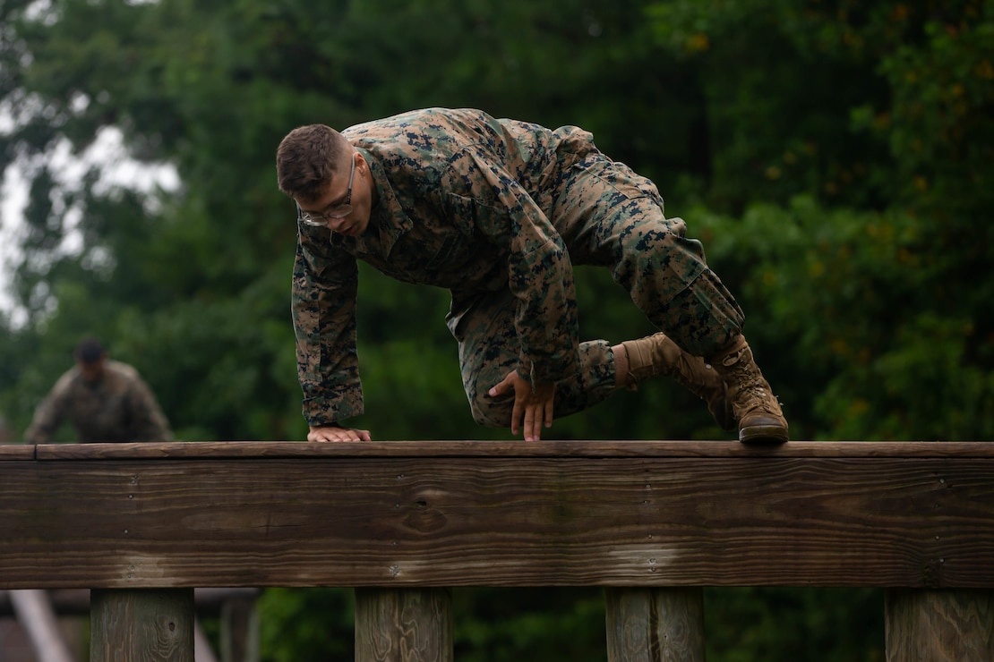 U.S. Marine Corps Lance Cpl. Connor Florence, a native of Littleton, Colo., and an antitank missile gunner with 1st Battalion, 2d Marine Division (MARDIV), jumps over an obstacle during a physical assessment on Camp Lejeune, N.C., Aug. 3, 2021. The Marines of 2d MARDIV's experimental battalion underwent a physical assessment consisting of a 500 meter swim, a five-mile run and the Marine Corps' obstacle course to establish a baseline for measuring success throughout the predeployment training program. (U.S. Marine Corps photo by Lance Cpl. Jennifer Reyes)