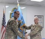 two military officers pass a flag