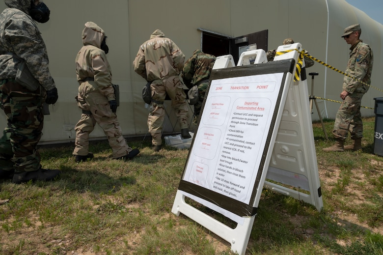 People in chemical gear line up outside a building near a sign with instructions written on it.