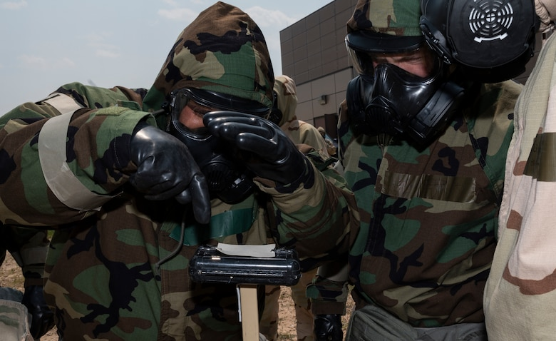 People dressed in chemical gear examine a piece of paper outside.