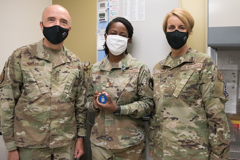 Three Airmen in group photo, middle Airman holding coin