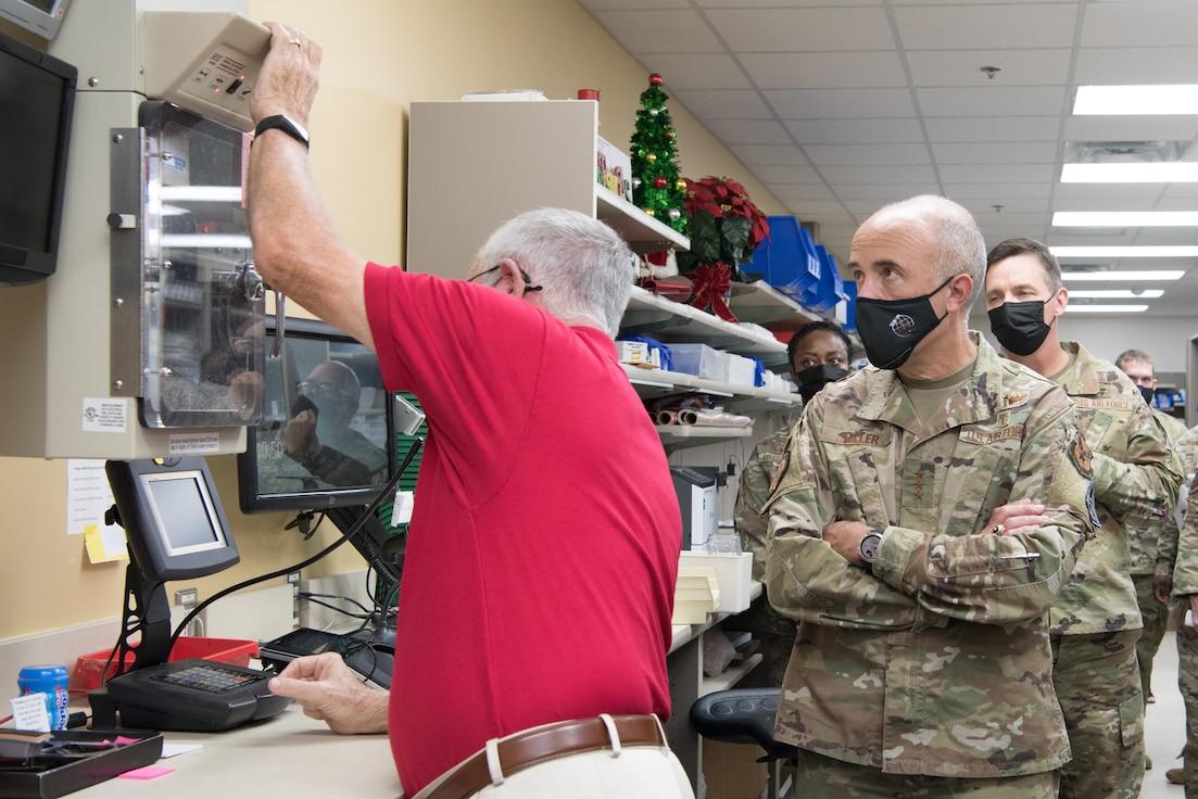 Lt. Gen. Miller watching pharmacy volunteer load a pneumatic tube