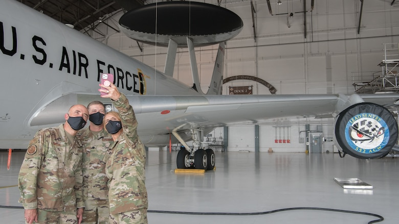 Three Airmen posing for selfie photo in front of E-3 aircraft