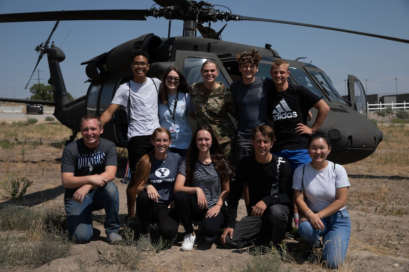 Freedom Academy delegates pose fo a photo in front of a helicopter