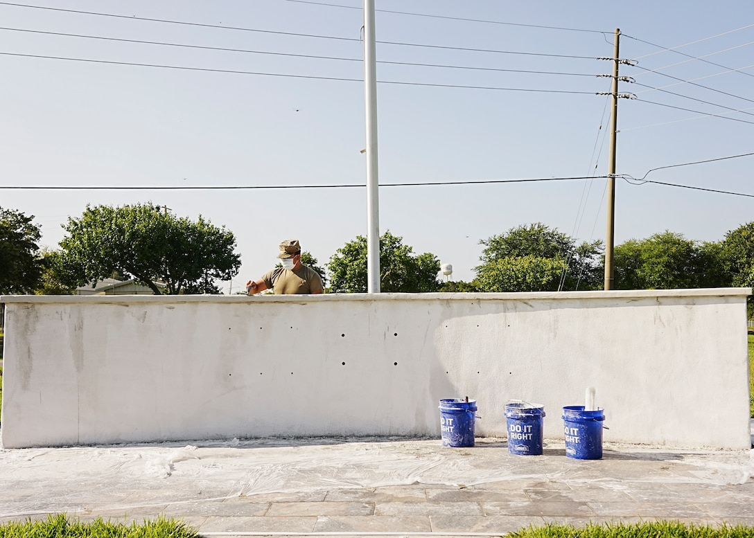 Airman behind concrete wall smooths stucco over surface.