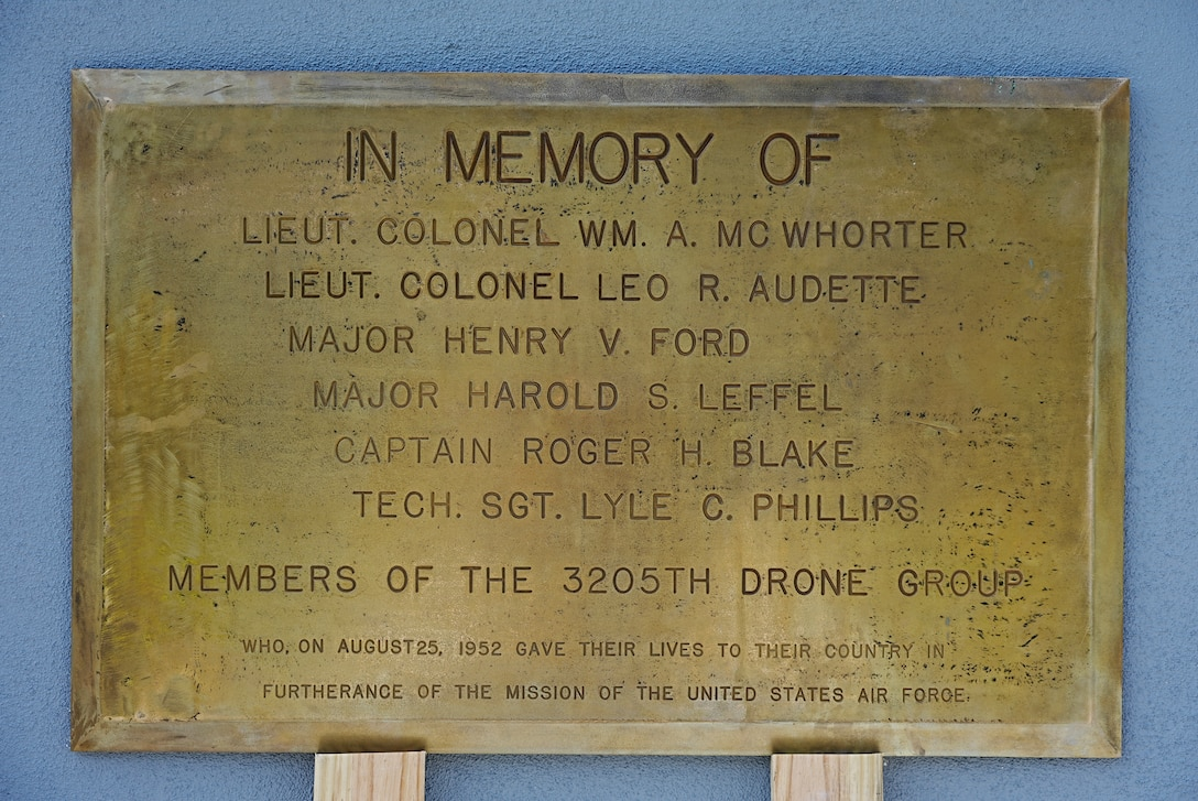 Gold plaque sits on two planks while leaning on concrete wall.