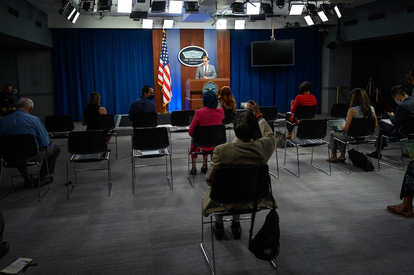A man,standing at a lectern, speaks to a group of socially distanced reporters. The sign behind him indicates that they are at the Pentagon.