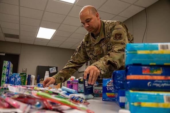 An Airman arrange donated items on a desk