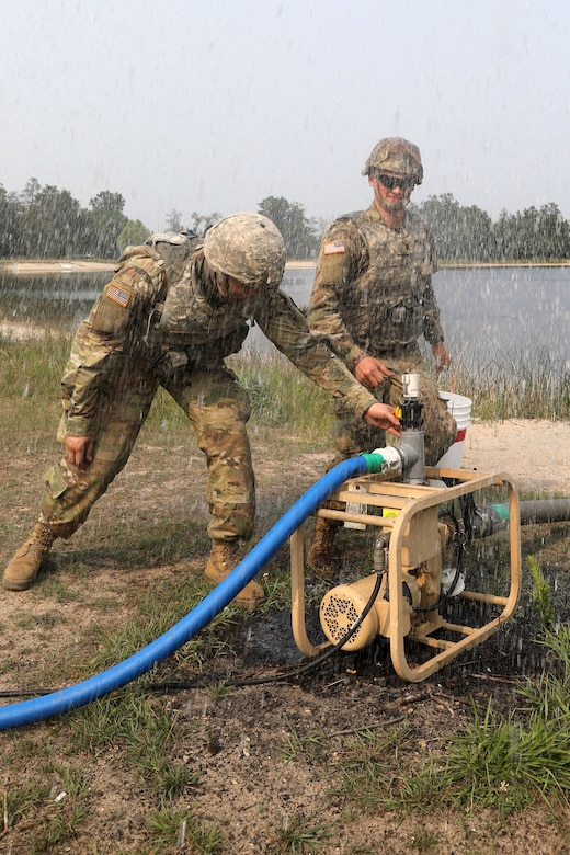 U.S. Army Cpl. Noah Borges and Spc. Garth Heinrich, water treatment specialists assigned to the 1034th Composite Supply Company, 185th Combat Sustainment Support Battalion, Iowa Army National Guard, prime the raw water pump in preparation to purify water at Howe's Lake, Camp Grayling Joint Maneuver Training Center, Michigan, during Northern Strike 21-2, Aug. 4, 2021. The 1034th CSC has supplied all water assets across the entire Northern Strike area of operations at Camp Grayling.