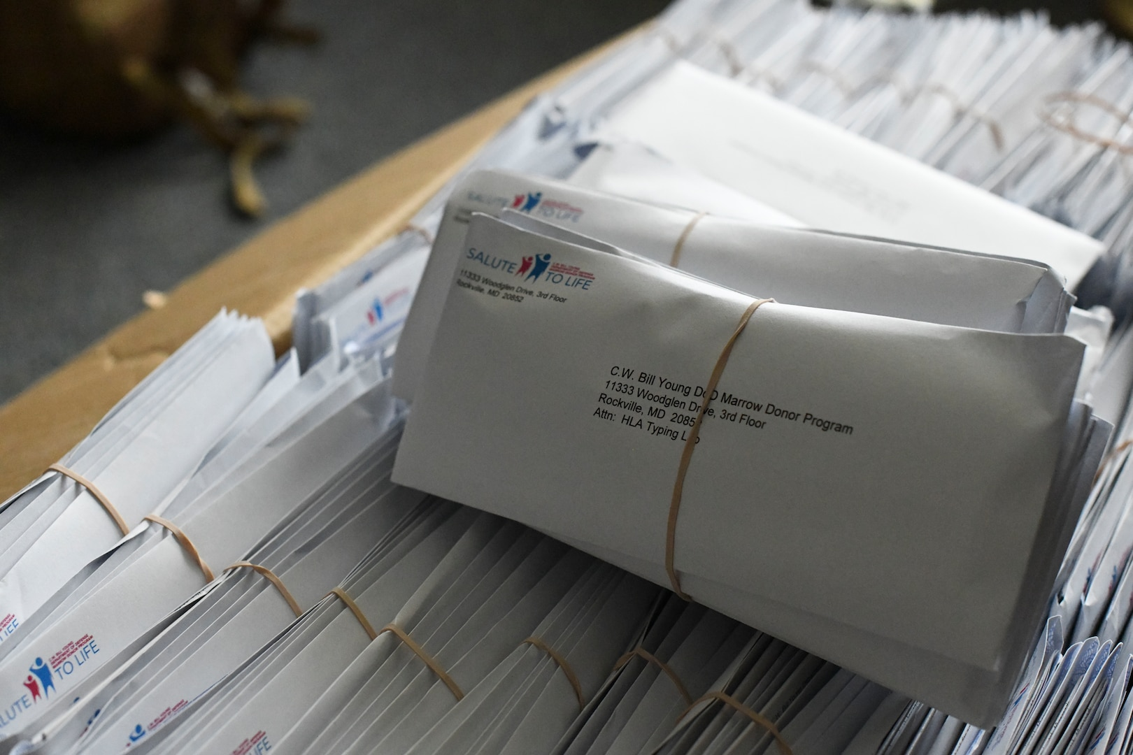 Envelopes are piled together in a box.