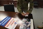 Female uniformed member swabs inner cheek for bone marrow donor registration