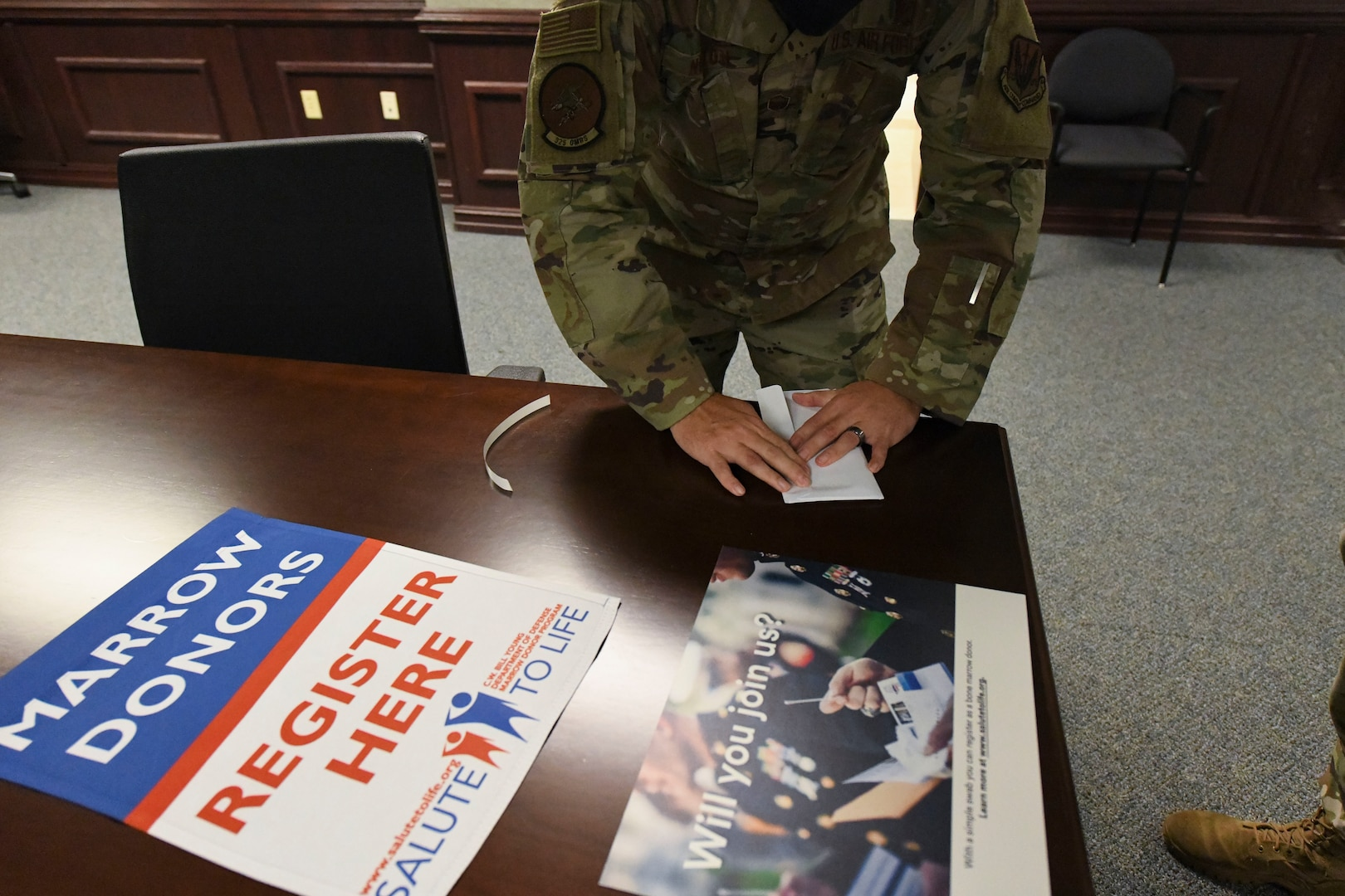 A uniformed member seals an envelope on a table.