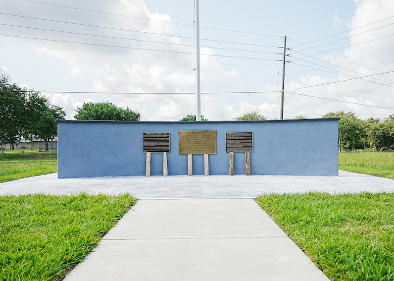 Concrete wall with plaques and flagpole with sidewalk leading to tile plaza around monument.