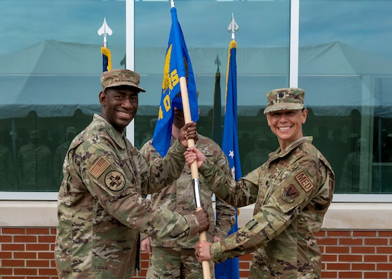 Lt. Col. Hatie McAviney, right, 4th Operational Medical Readiness Squadron incoming commander, receives the guidon from Col. Dolphis Hall, 4th Medical Group commander during the 4th OMRS assumption of command ceremony at Seymour Johnson Air Force Base, North Carolina, August 6, 2021.