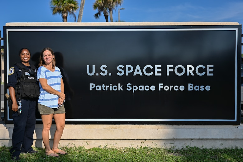 Christy Kalicharan (left), 45th Security Forces Squadron police officer and Gretta Lowry (right), Cocoa Beach, Florida, resident pose for a group photo at Patrick Space Force Base, Florida, July 28, 2021. Kalicharan provided life saving aid to Lowry after she was bitten by a shark while surfing.