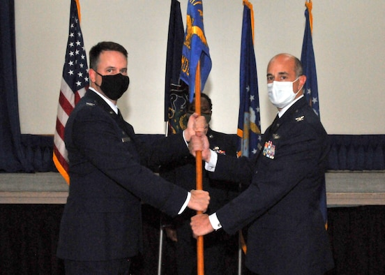 An Air Force colonel hands a guidon to a new commanding officer.