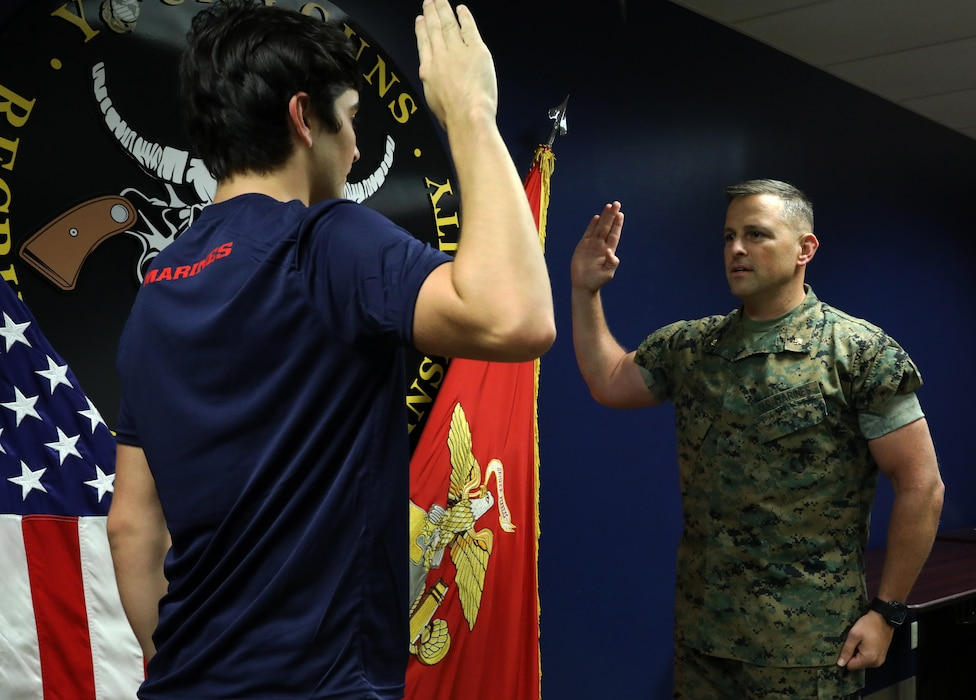 Daniel Hayek (left) takes his Oath of Enlistment from his father, Maj. Richard Hayek, the Commanding officer of Marine Corps Recruiting Station Kansas City, before signing an active duty contract with the U.S. Marine Corps at Kansas City Military Entrance Processing Station in Kansas City, Mo., July 26, 2021. By committing to the Marines, Daniel is poised to become a fourth-generation service member in his family-- following the footsteps of his mother, father, grandfather and great-grandfather. Daniel graduated from Navarre High School in Navarre, Fla., in 2020.