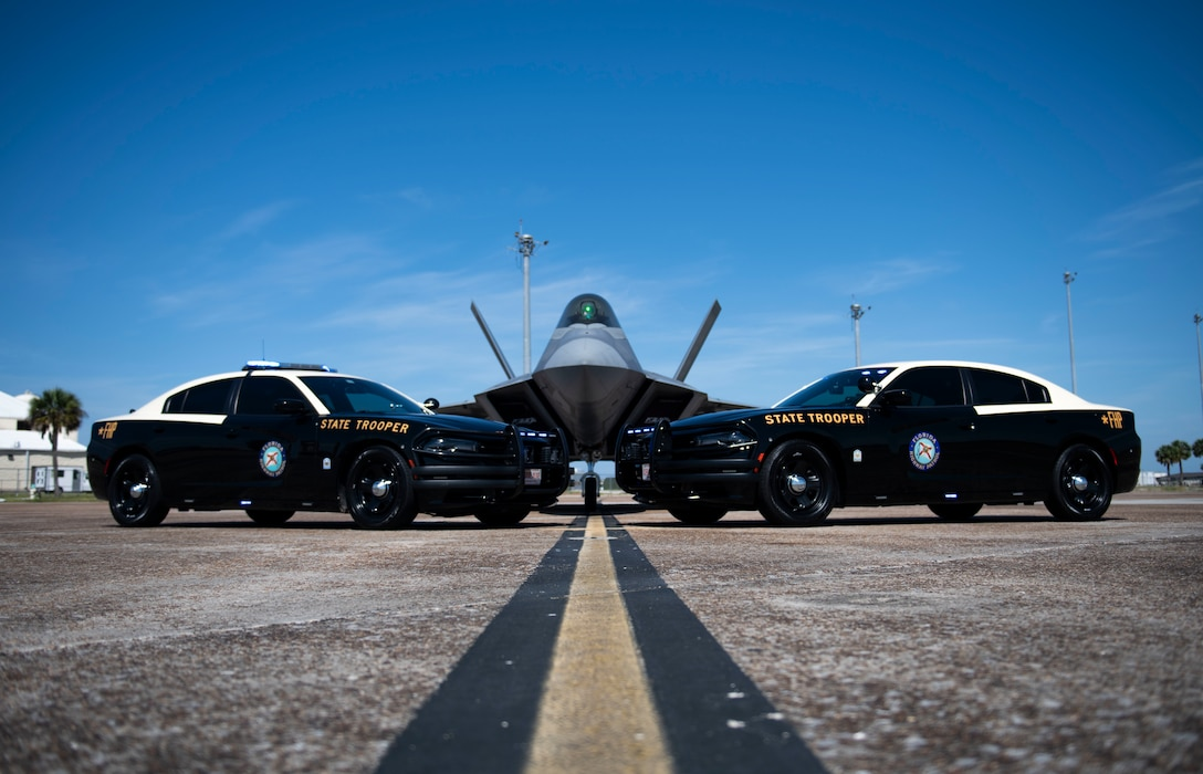 Two cars and an airplane are posed for a photo op