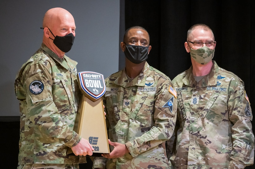 """Gen. John W. """"Jay"""" Raymond, U.S. Space Force chief of space operations, and Chief Master Sgt. of the Space Force Roger A. Towberman, pose for a photo with Tech. Sgt. Maurice Moyer, team captain for the Department of the Air Force Gaming League's Space Force Team, while he holds the Call of Duty Endowment Bowl Trophy. The Space Force team were the season one tournament winners."""