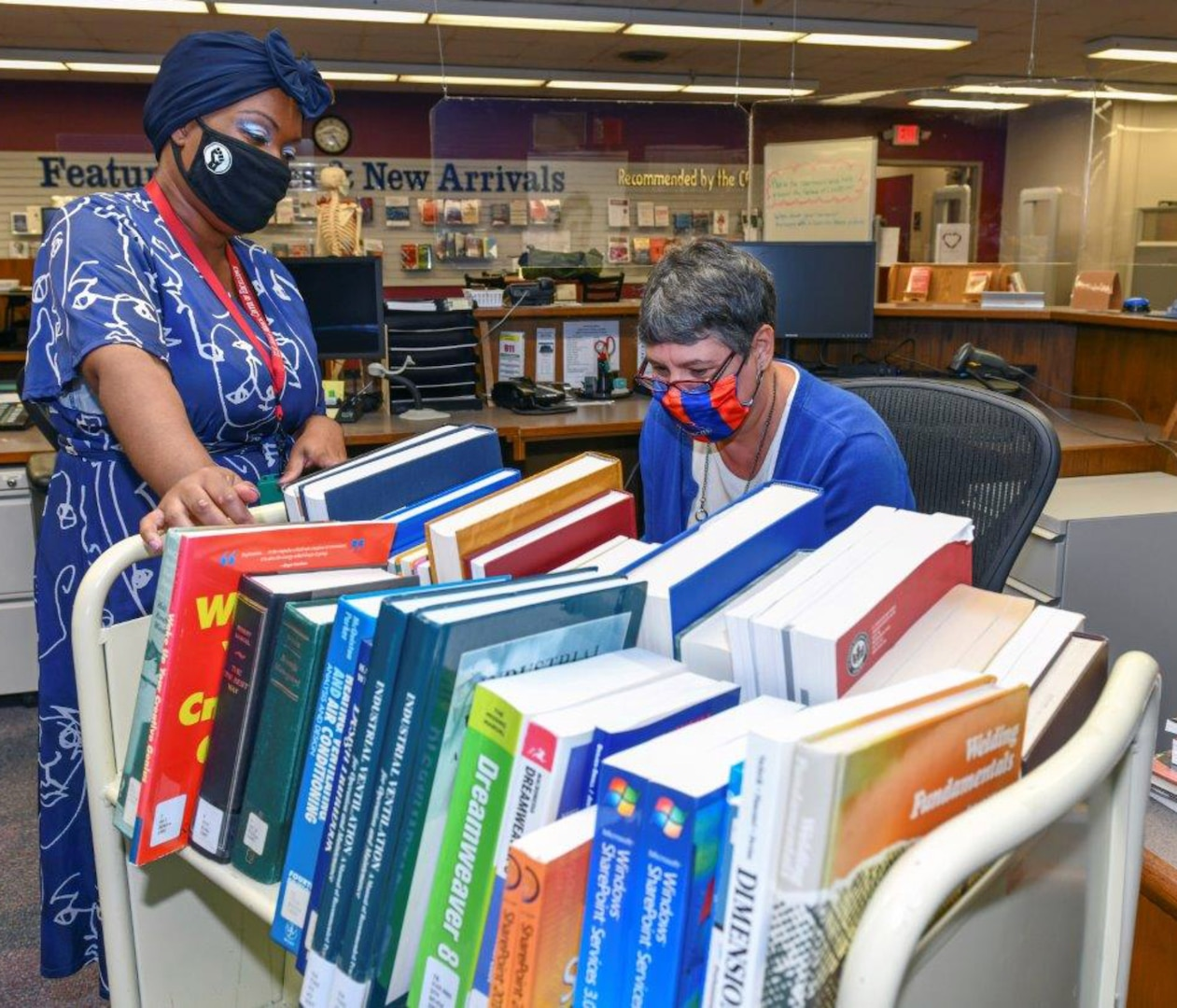 Jodi Quesnell (right), Stimson Library director, and library technician Lakeitra Spight look through a cart of books before placing them on the shelves.