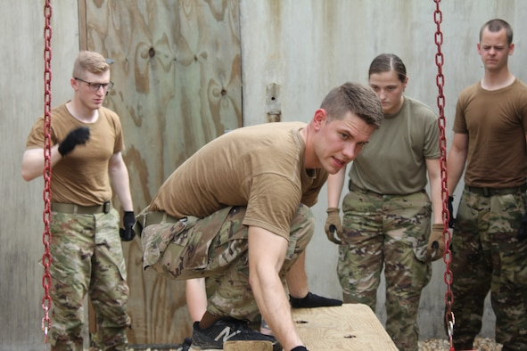 An Air Force ROTC cadet works his way through one of the obstacles on the Leadership Reaction Course