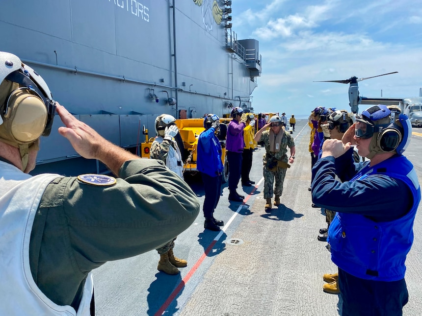ATLANTIC OCEAN (Aug. 10, 2021) Chief of Naval Operations (CNO) Adm. Mike Gilday walks through rainbow sideboys after landing aboard the Wasp-class amphibious assault ship USS Kearsarge (LHD 3). (U.S. Navy photo by Cmdr. Nathan Christensen/Released)