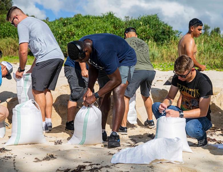 海兵隊員らが豊原地区のシーグラスビーチで、損傷した道路を補修するためのサンドバッグに砂を詰める。