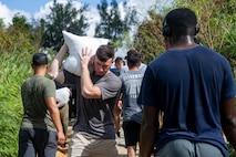 海兵隊員らが豊原地区のシーグラスビーチで、損傷した道路を補修するためにサンドバッグを搬送。
