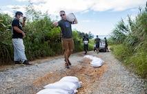 海兵隊員が豊原地区のシーグラスビーチで、地区職員に確認をとりながら損傷した道路を補修するためにサンドバッグを運びます。