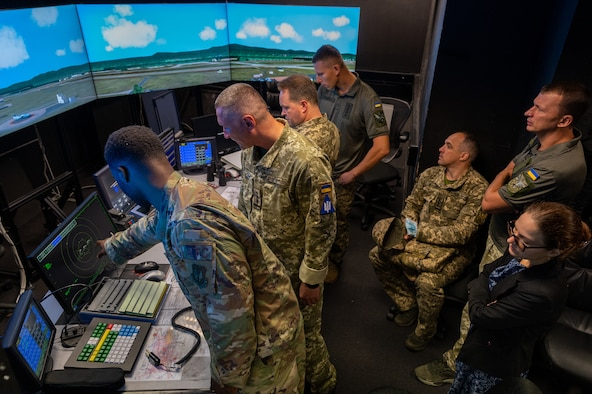 Service members standing in an air traffic control tower.