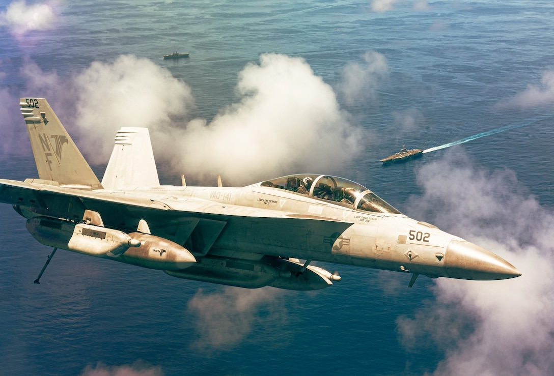 """ARABIAN SEA (Aug. 9, 2021) – Lt. Derrick Petett and Lt. Melissa Deardorff, pilots assigned to the """"Shadowhawks"""" of Electronic Attack Squadron (VAQ) 141, fly an EA-18G Growler above USS Ronald Reagan (CVN 76) over the Arabian Sea, Aug. 9. VAQ-141 is attached to Carrier Air Wing 5, the air wing of Commander, Task Force 50, deployed to the U.S. 5th Fleet area of operations in support of naval operations to ensure maritime stability and security in the Central Region, connecting the Mediterranean and Pacific through the western Indian Ocean and three strategic choke points. (U.S. Navy photo by Electronic Attack Squadron (VAQ) 141)"""