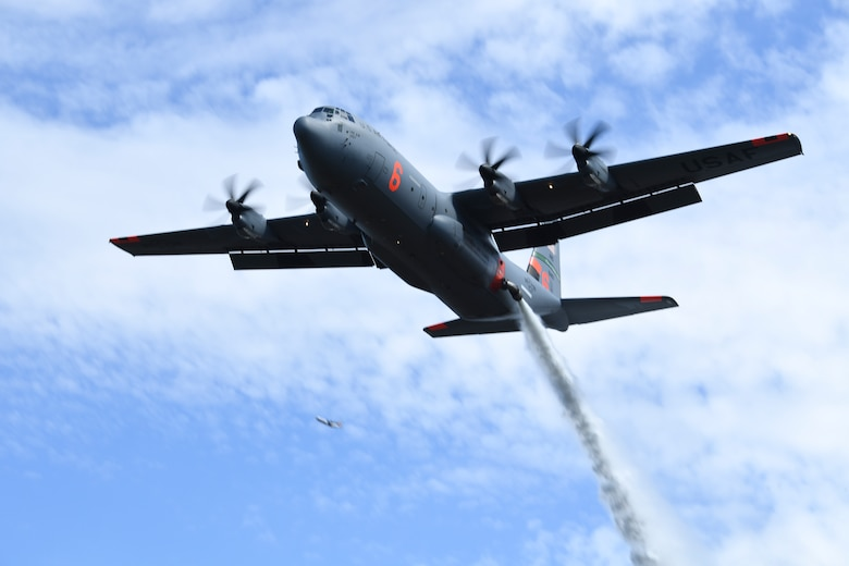 A MAFFS C-130 aircraft drops a water load in the Tahoe National Forest for a training exercise.