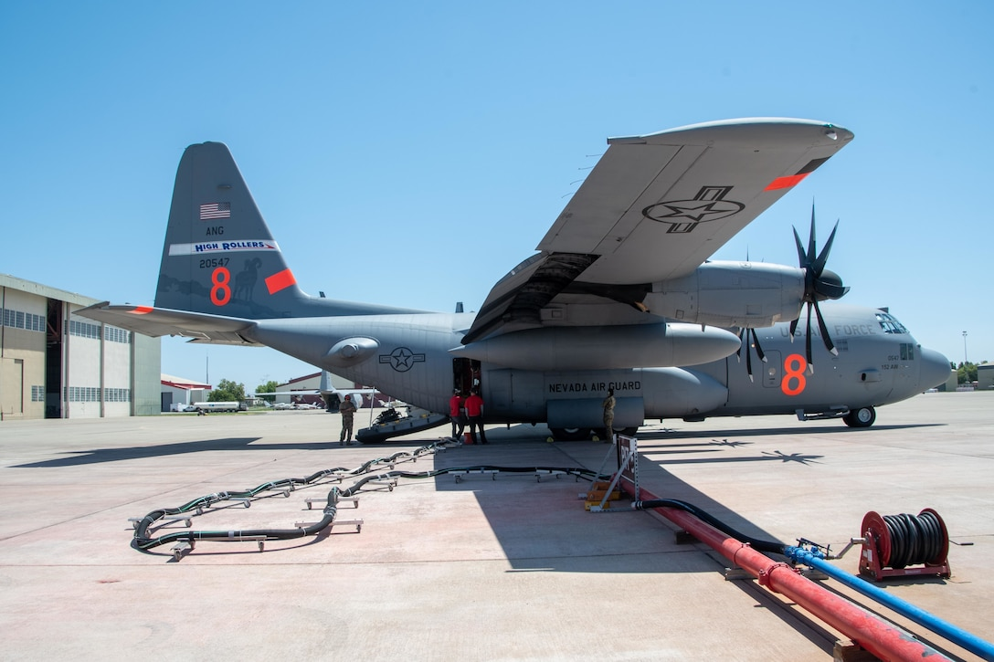 """CAL FIRE employees load retardant into the MAFFS system of an Air National Guard C-130, designated """"MAFFS 8 out of Reno, Nev."""" July 13, 2021, from CAL FIRE Air Tanker Base, McClellan Park, Calif."""