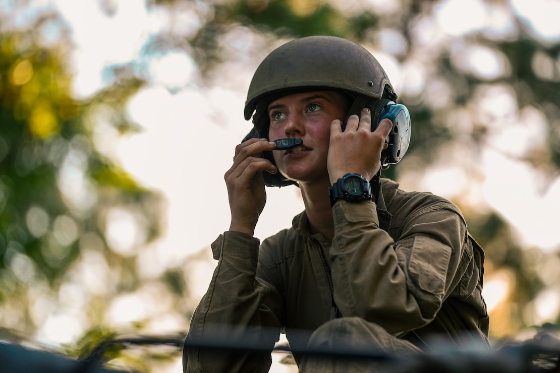 U.S. Marine Corps Lance Cpl. Maelynn Ruff, a native of Elberton, Ga. and an assault amphibious vehicle operator with Alpha Company, 2d Assault Amphibian Battalion, 2d Marine Division, checks communication connectivity before a wet-gap amphibious crossing as part of a company-sized infiltration on Camp Lejeune, N.C., Aug. 10, 2021. The infiltration focused on maneuvering across complex terrain and picket lines with near-peer capabilities in an unscripted force-on-force scenario. (U.S. Marine Corps photo by Lance Cpl. Jacqueline C. Arre)