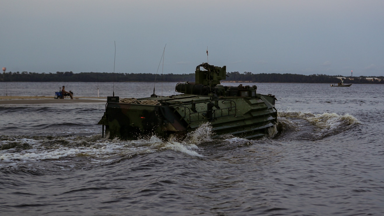 An AAV7A1 assault amphibious vehicle conducts a wet-gap amphibious crossing as part of a company-sized infiltration on Camp Lejeune, N.C., Aug. 10, 2021. The infiltration focused on maneuvering across complex terrain and picket lines with near-peer capabilities in an unscripted force-on-force scenario. (U.S. Marine Corps photo by Lance Cpl. Jacqueline C. Arre)