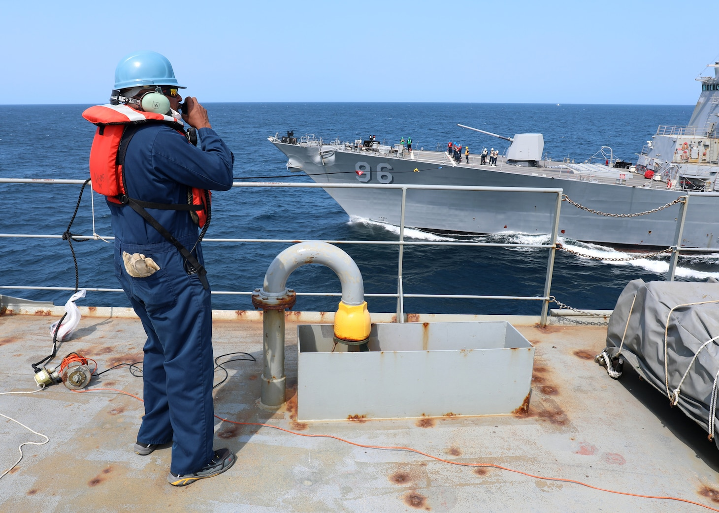 A Civil Service Mariners, serving aboard Military Sealift Command's fleet replenishment oiler USNS Joshua Humphreys (T-AO 188), communicates with the guided missile destroyer USS Bainebridge (DDG 96) by way of sound powered telephone via the telephone and distance line, during an underway replenishment-at-sea in the Atlantic Ocean, July 17.
