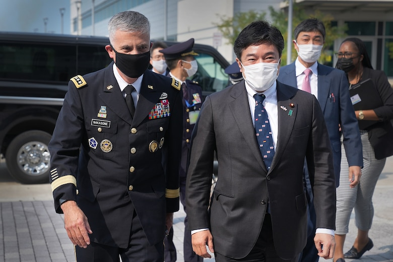 A U.S. Army general walks next to a Japanese government leader, both men wearing face masks.