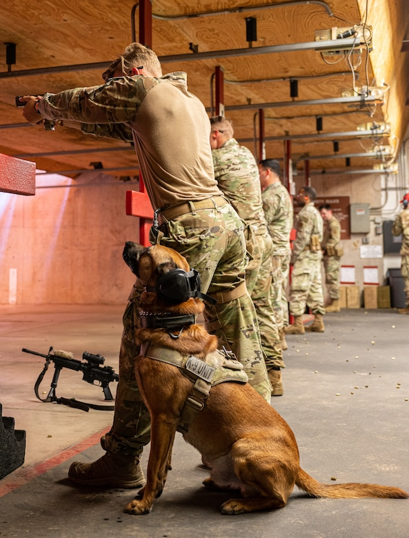 U.S. Air Force Senior Airman Noah Huff, 56th Security Forces Squadron military working dog handler, fires a weapon next to MWD Enzo, during a weapons qualification course Aug. 3, 2021, at Luke Air Force Base, Arizona.