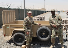 Army Reserve Col. Matthew Hirsch, the acting director of the Counter ISIS, Equip, Train Fund-Iraq, stands with Sgt. 1st Class Andrew Wright, the CTEF-I transportation manager, stand with a trailer moments before its July 7, 2021 pickup as the last CTEF-I items that were once parked in Camp Arifjan, Kuwait's Lot 54. This trailer, and the other items in the last batch, were delivered to Iraqi security forces as part of CTEF-I's mission to bolster military partner capacity. The two men deployed to the camp with the Army Reserve's Indianapolis-based 310th Sustainment Command.