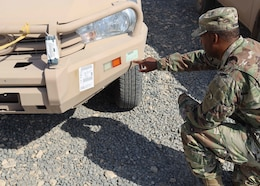 Army Reserve Sgt. 1st Class Andrew Wright, the Counter ISIS, Train Equip Fund-Iraq transportation manager, July 7, 2021 verifies the tracking tag for one of the up-armored pickup trucks that made up with six trailers that last CTEF-I items in Camp Arifjan, Kuwait's Lot 54. Wright, who deployed to the camp with the Indianapolis-based 310th Sustainment Command (Expeditionary) said he is incredibly proud these last pieces close out the inventory of items parked in the lot. This truck and other items in the last batch were delivered to Iraqi security forces as part of CTEF-I's mission to bolster military partner capacity.