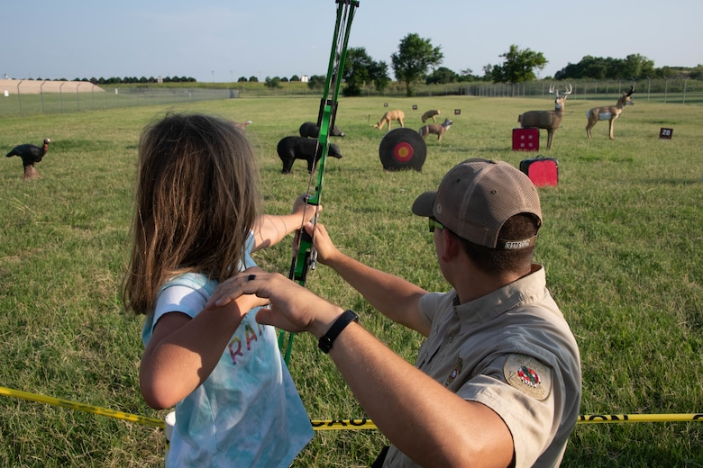 Daniel Perkins, Oklahoma Department of Wildlife Conservation state game warden helps Genevieve Allen, daughter of U.S. Air Force Master Sgt. Nathan Allen, 97th Air Mobility Wing public affairs superintendent, shoot her bow on Altus Air Force Base, Oklahoma, July 30th, 2021. Outdoor recreation supports family and individual well being, unit cohesion, and fitness through many programs and facilities on base. (U.S. Air Force photo by Airman 1st Class Trenton Jancze)