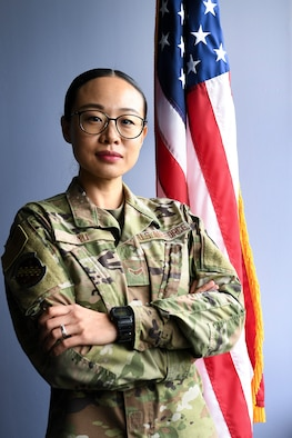 Airman 1st Class Ling Yu, 66th Comptroller Squadron financial accounting technician, stands by a flag in the 66 CPTS conference room at Hanscom Air Force Base, Mass., Aug. 10. Yu received her U.S. citizenship July 23. (U.S. Air Force photo by Lauren Russell)