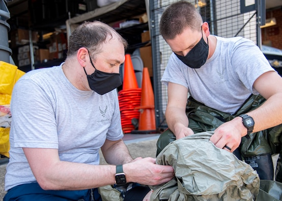 First Lt. (Dr.) Thomas Brown, left, 436th Operational Medical Readiness Squadron Warfighter Clinic physician assistant, and Tech. Sgt. Timothy Jenkins, 436th Medical Support Squadron diagnostic imaging section chief, inspect a decontamination suit during in-place patient decontamination training at Dover Air Force Base, Delaware, Aug. 11, 2021. The IPPD training helps Airmen practice decontaminating patients affected by chemical, biological, radiological, nuclear or high-yield explosive weapons attacks before entering the clinic for further care. (U.S. Air Force photo by Tech. Sgt. Nicole Leidholm)