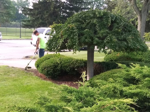 88th Civil Engineer Squadron equipment operator, trims  weeds and hedges at Air Force Materiel Command headquarters.