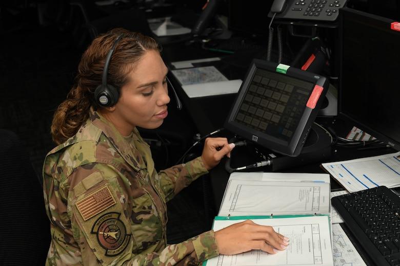 U.S. Air Force Airman 1st Class Yara Martinez looks over a binder.