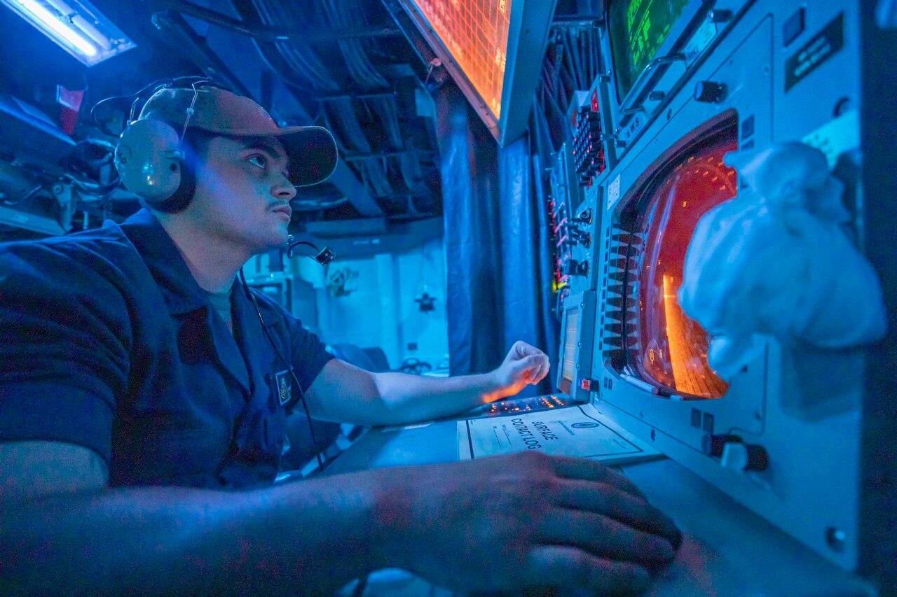 A sailor monitors a radar screen.