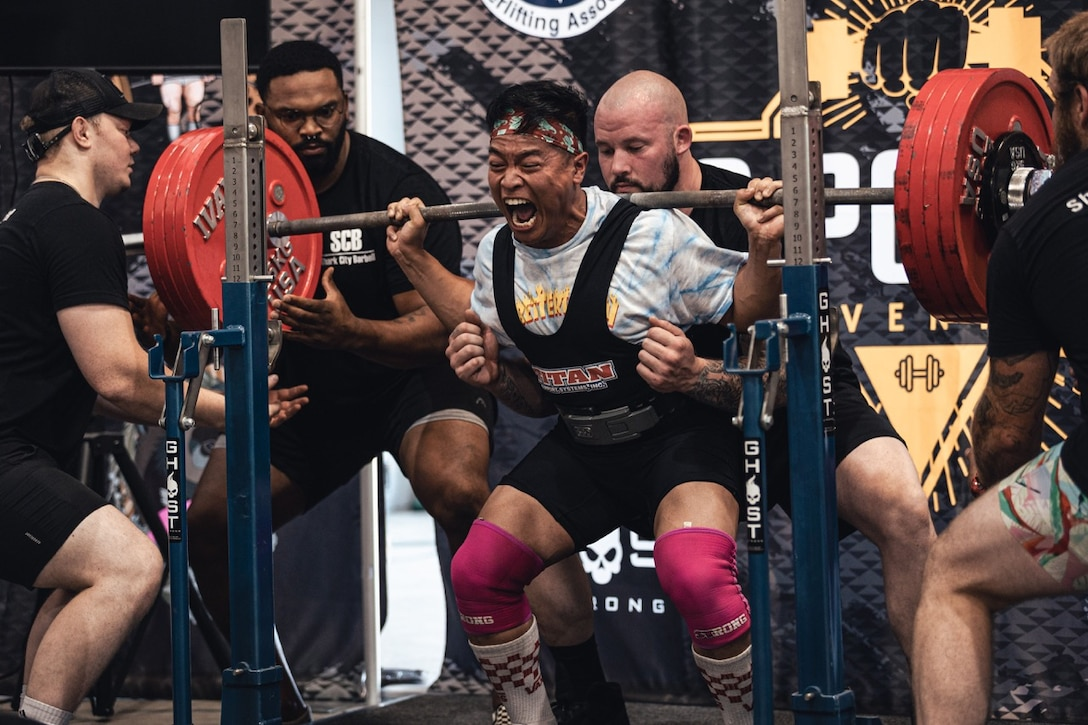 U.S. Marine Corps Cpl. Sean Nguyen completes a maximum repetition on bench squat.