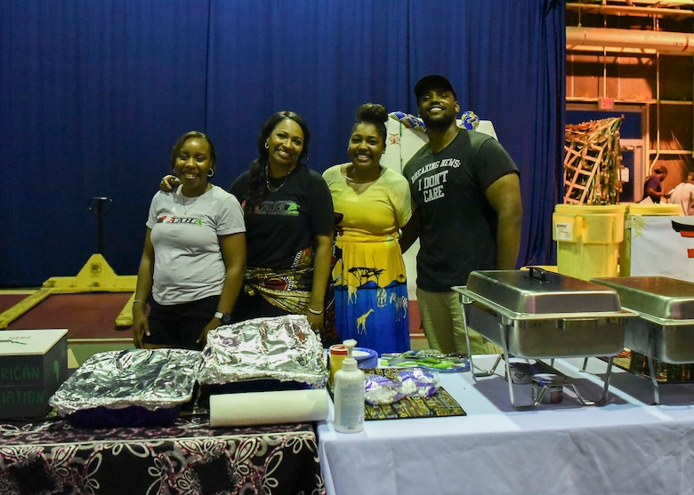 African American Heritage Association members pose for a picture standing behind their booth.