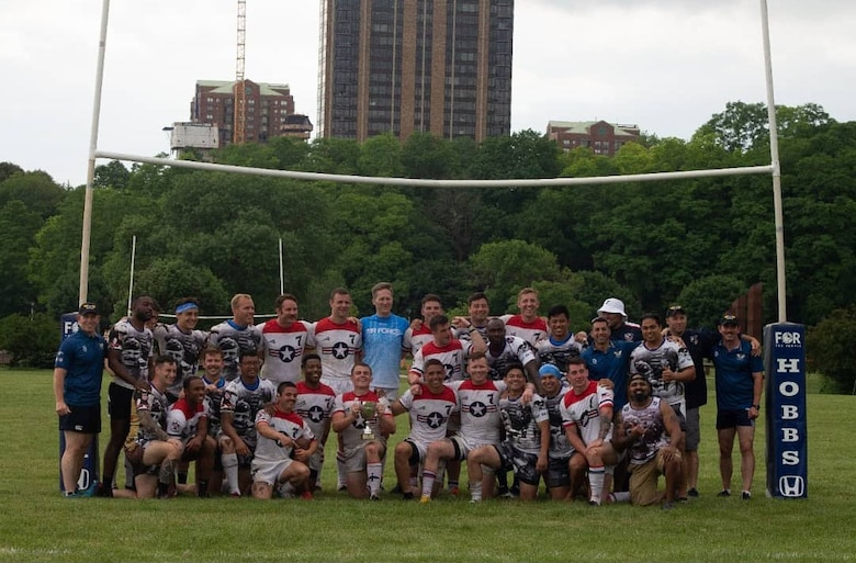 A team of rugby players stand together in front of goal.